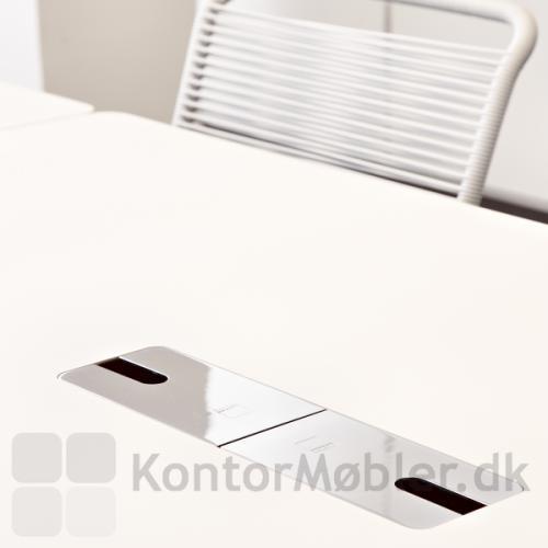 Close-up af forkromet kabelgennemføring med klap - her i bord med hvid laminat