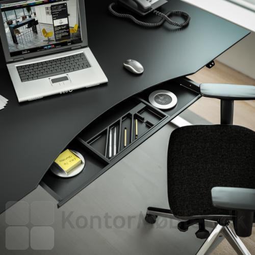 Delta hævesænkebord med sort overflade og udtræksskuffe til opbevaring af kontorartikler og lignende sager som du bruger i løbet af en arbejdsdag.