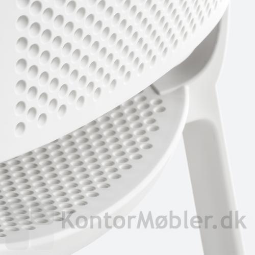 Dome stol i hvid med fokus på de hullede detaljer