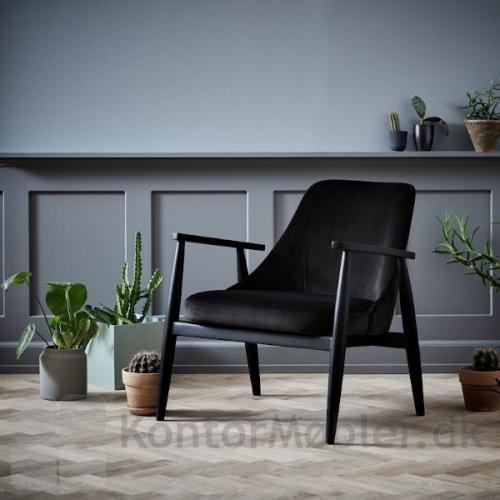 Saga Loungestol i sort velour og sorte ben i asketræ. Armlæn er ligeledes i sort asketræ.