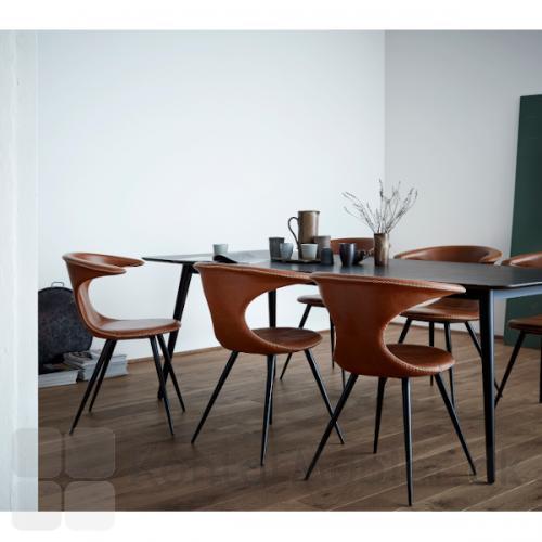 Flair stol med polstring i lysebrun læder og koniske sorte ben. Her elegant sat sammen med et sort spisebord.