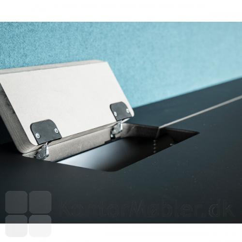 Delta bord med sort højtryks laminat bordplade og med lågeklap og slids til at gemme ledninger væk.