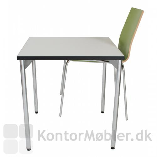 Grøn Spela stol ophængt på hvidt bord med ophængsbeslag..