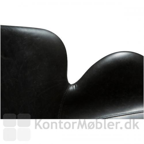 Gaia Loungestol med sort kunstlæder polstring. Stolen har lækre former og flotte synlige syninger i polstringen