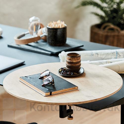 Rundt bord med bordbeslag, som giver et personligt og afgrænsende præg på det åbne kontor med mange arbejdspladser.