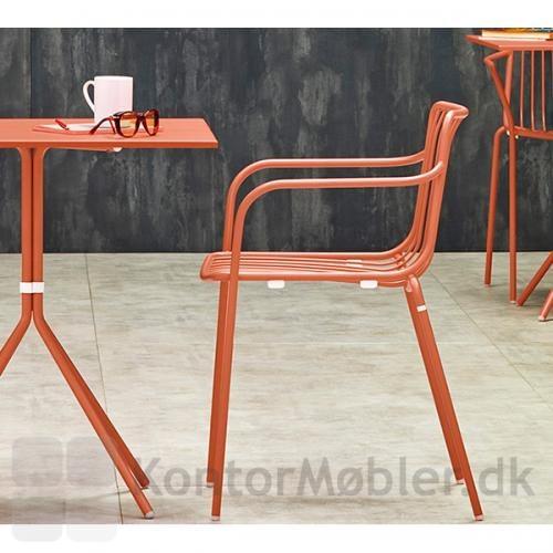 Nolita udendørs stol til café eller terrasse, her vist med lav ryg og armlæn i farven koral
